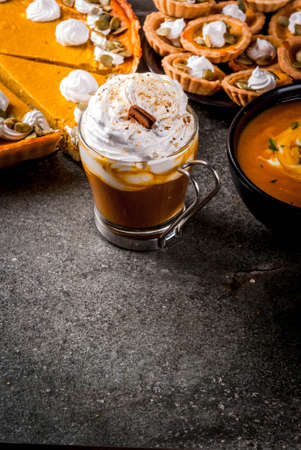 Set of traditional autumn food. Halloween, Thanksgiving. Spicy pumpkin latte, pumpkin pie and tartalets with whipped cream and pumpkin seeds, pumpkin soup, on black stone table. Copy space