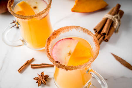 Halloween, Thanksgiving. Traditional autumn, winter drinks and cocktails. Spicy hot pumpkin sangria, with apple, cinnamon, anise. On a white marble table, in glass mugs. Selective focus, close view