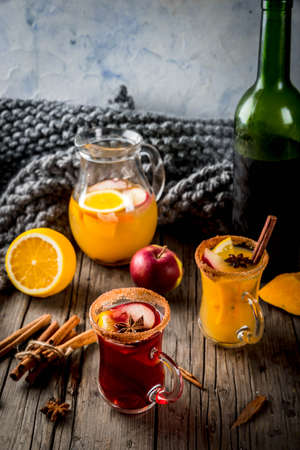 Traditional fall and winter drinks and cocktails. White and red autumn hot spicy sangria with anise, cinnamon, apple, orange, wine. In glass mugs, old rustic wooden table. Selective focus copy space