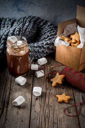 Traditionele herfstwinter drankjes en lekkernijen. Kopje warme chocolademelk met marshmallow en gember koekje sterren, in geschenkverpakking, oude rustieke houten tafel. Gezellige sfeer, kopie ruimte