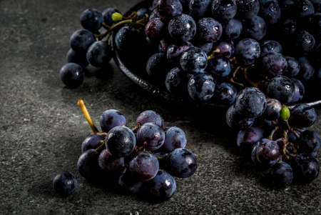 Raw natural organic farmers black grapes, bunches on black plate, dark stone background, copy space Banco de Imagens