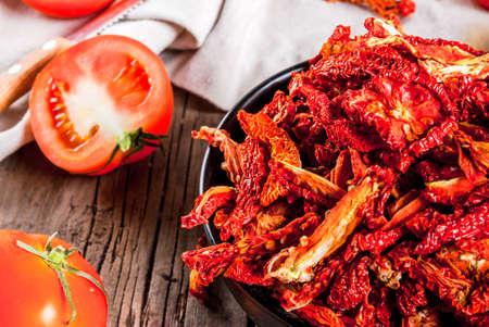自家製天日干し有機トマト、シャキッとしたトマト、新鮮なトマト、オリーブ オイルの古い素朴な木製のテーブル上のチップ。コピー スペース