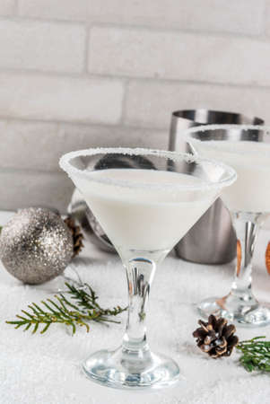 Ideas and recipes for Christmas drink. White Chocolate Snowflake Martini cocktail, on white marble table with Christmas decoration, copy space