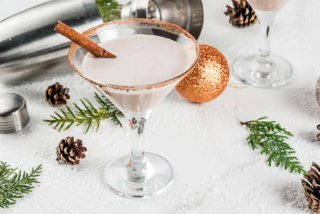 Ideas and recipes for Christmas drink. Eggnog martini, with cinnamon sticks, on white marble table with Christmas decoration, copy space Imagens - 88141117