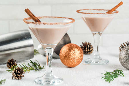 Ideas and recipes for Christmas drink. Eggnog martini, with cinnamon sticks, on white marble table with Christmas decoration, copy space