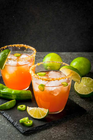 Alcohol. Traditional Mexican South American cocktail. Spicy michelada with hot jalapeno peppers and lime. On a dark stone table. Copy space Imagens