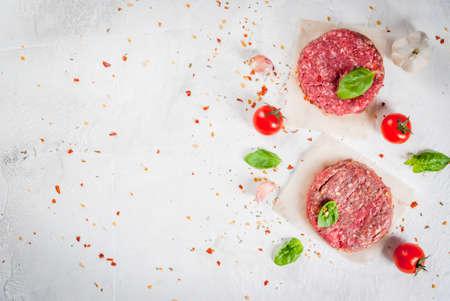 De verse ruwe eigengemaakte fijngehakte biefstukhamburger met kruiden, de tomaten en het basilicum, op een witte steen betonnen lijst, kopiëren ruimte, hoogste mening