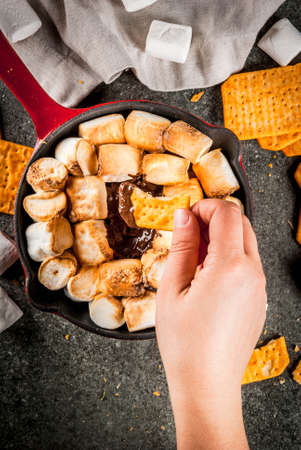 Indoor s'mores, baked s'mores dip in a cast iron skillet pan with graham crackers. Girls hand in picture, tasting smores, dark grey table, top view copy space