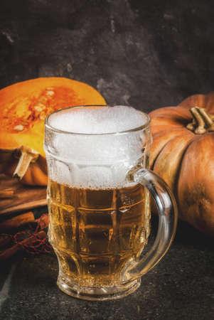 Schuimig kruidig pompoenaal of bier in glasmok, op zwarte achtergrond, exemplaarruimte Stockfoto