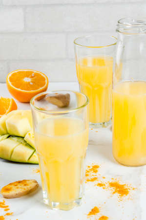 Indian cuisine recipes. Healthy food, detox water. Traditional Indian mango, orange, turmeric and ginger smoothie, on a white marble table. Copy space