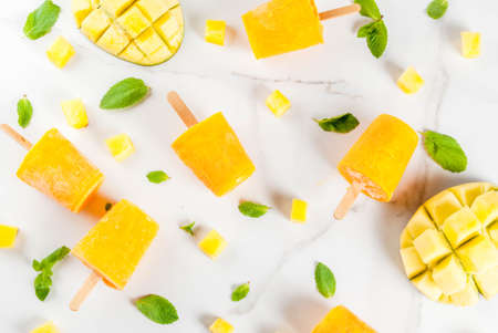 Ice cream, popsicles. Organic dietary foods, desserts. Frozen mango smoothie, with mint leaves and fresh mango fruit, on a white marble table. Copy space top view Stock Photo