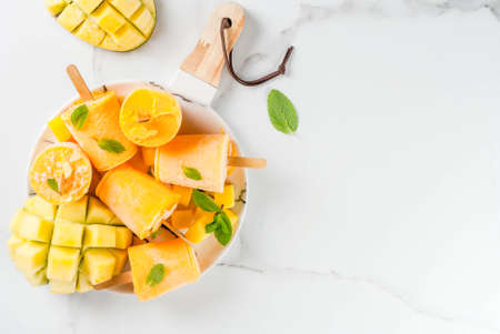 Ice cream, popsicles. Organic dietary foods, desserts. Frozen mango smoothie, with mint leaves and fresh mango fruit, on plate, on white marble table. Copy space top view Stok Fotoğraf - 88531256