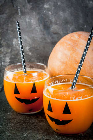 Ideas for a childrens and party of Halloween treats. Pumpkin orange cocktail in glasses, decorated with a pumpkin jack lantern, on a black stone table. Copy space Stock Photo