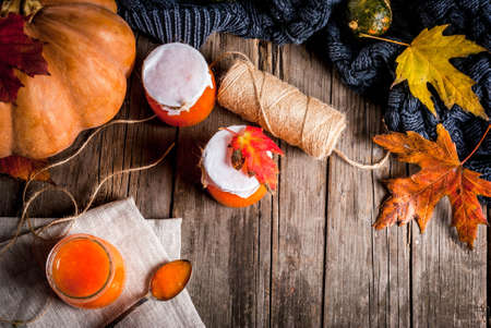 Autumn recipes, dishes from a pumpkin. Sweet spicy pumpkin jam in a serving jar, with a spoon, on an old rustic wooden table decorated with pumpkins, autumn leaves, a blanket. Top view copy space