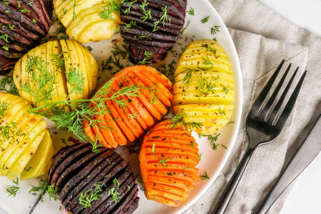 Ideas of vegan food, autumn recipes from vegetables. Roasted Hasselback Beets, carrots, potatoes, with fresh herbs, on a plate, on a white marble background, top close view