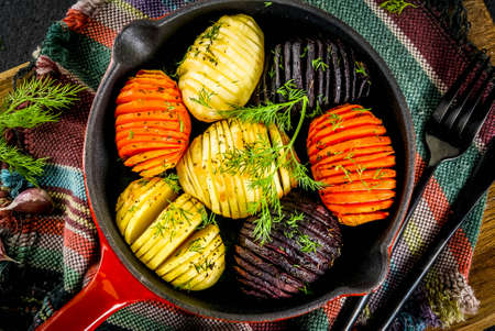 Ideas of vegan food, autumn recipes from vegetables. Roasted Hasselback Beets, carrots, potatoes, with fresh herbs, in a frying pan, on a black stone table, copy space top view Banco de Imagens