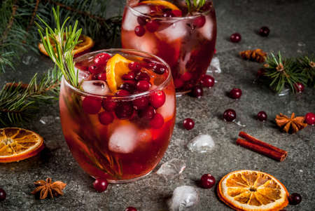 Weihnachtswinter Getränke. Kaltes Cocktail mit Moosbeeren, Orange, Rosmarin, mit Gewürzen (Zimt, Anis) und Eis, auf einer dunklen Steintabelle, Kopienraum Standard-Bild