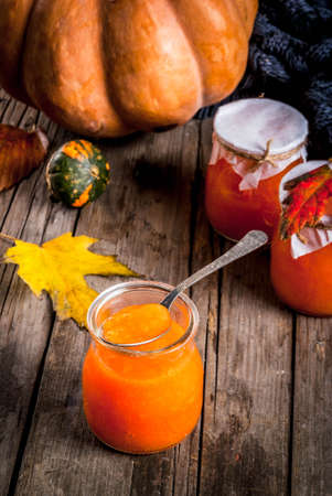 Autumn recipes, dishes from a pumpkin. Sweet spicy pumpkin jam in a serving jar, with a spoon, on an old rustic wooden table decorated with pumpkins, autumn leaves, a blanket.Copy space