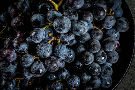 Raw natural organic farmers black grapes, bunches on black plate, dark stone background, top close view Imagens