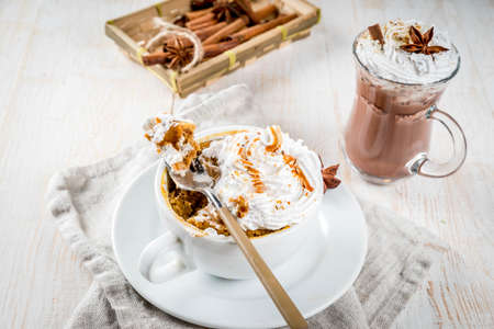 Recipes with pumpkins, fast food, microwave meal. Spicy pumpkin pie in mug, with whipped cream, ice cream, cinnamon, anise. On white wooden table, with cup of hot chocolate. Copy space 版權商用圖片