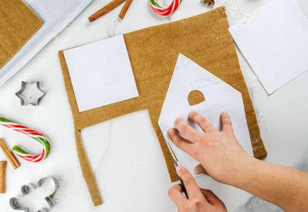 Voorbereidingen treffen voor Kerstmis, een persoon, handen in het kader, maakt een peperkoek huis. Snijden op een papieren sjabloon uit het deeg, bakplaat, decoratie in het frame. Op een witte tafel, kopie ruimte bovenaanzicht