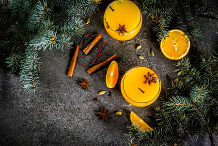 Fall, winter cocktails, Hot spicy winter orange punch with cinnamon, anise stars, cardamom, cloves. On black stone table, with ingredients and christmas tree branches, in glasses. Copy space top view Stock Photo