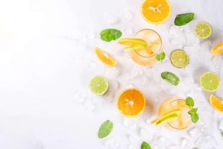 ビタミン夏ドリンクします。オレンジとライム、ミントの小枝、シトラス パンチは、氷で冷やしています。成分と、白い大理石のテーブルにコピー  写真素材