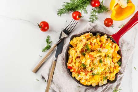 Mexican food recipes, Revoltillo de Huevos, Scrambled Eggs a la Dominicana, in portioned skillet, on white marble table,copy space top view