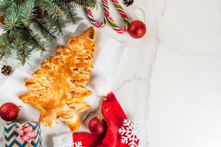 Snacks for Christmas party. Closed pizza from puff pastry in the form of a Christmas tree. On a white marble table. With Christmas decorations. top view copy space