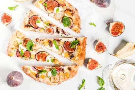 Autumn baking recipes. Sweet pie pizza or fruit focaccia with figs, pears, grapes, cream cheese, walnuts and mint. With white wine glass, on white marble background, copy space top view