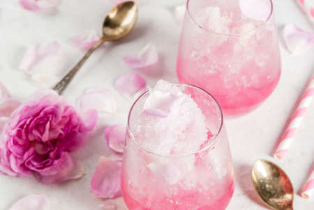 Summer refreshing desserts. Vegan diet food. Ice cream frozen rose, froze, with rose petals and rose wine. On a white concrete table, with spoons, striped straws, petals and rose flowers. Copy space