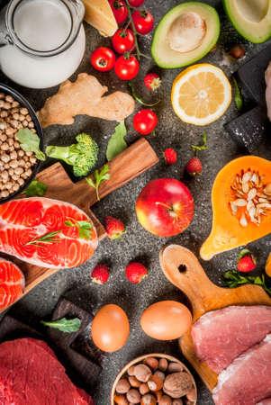 Gezonde voeding achtergrond. Biologische voedselingrediënten, superfoods: rund- en varkensvlees, kipfilet, zalmvis, bonen, noten, melk, eieren, fruit, groenten. Zwarte stenen tafel, kopie ruimte bovenaanzicht