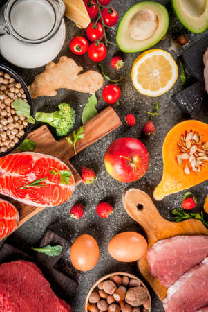 Healthy diet background. Organic food ingredients, superfoods: beef and pork meat, chicken filet, salmon fish, beans, nuts, milk, eggs, fruits, vegetables. Black stone table, copy space top view Stock Photo