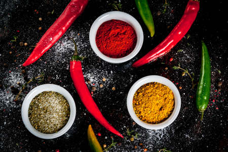 Various spices and seasonings. Cooking background.  Turmeric, curry, paprika, pepper, chili, dried basil, salt, fresh chili, thyme. Black rusty metal background. Top view
