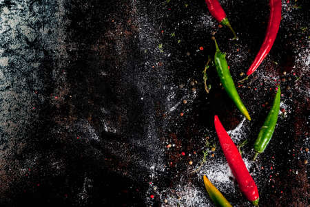 Spices for cooking. Spicy red and green chilli peppers on old metal rusty background, top view copy space
