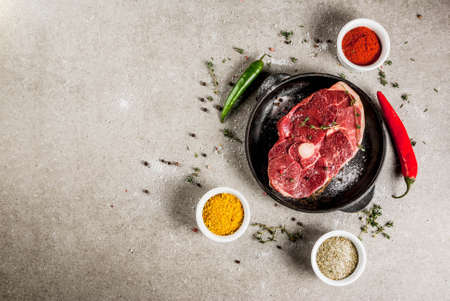 Fresh raw meat. A piece of lambs tenderloin, with a bone, with a cutting ax, with spices for cooking on grey stone table Top view copy space