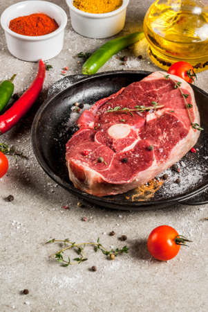 Fresh raw meat. A piece of lambs tenderloin, with a bone, with a cutting ax, with spices for cooking on grey stone table Copy space Stock Photo