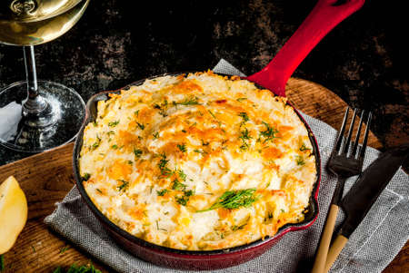 Skillet Shepherd's Pie, british casserole in cast iron pan, with minced meat, mashed potatoes and vegetables, on dark rusty background, copy space