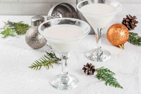アイデアやクリスマスの飲み物のためのレシピ。ホワイト チョコレート スノーフレーク マティーニ カクテル、クリスマスの装飾と白い大理石テー