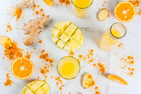 Indian cuisine recipes. Healthy food, detox water. Traditional Indian mango, orange, turmeric and ginger smoothie, on a white marble table. Copy space top view Stock Photo