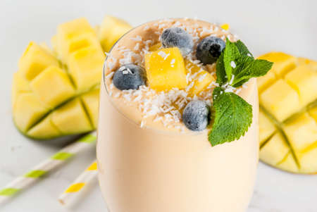 Dietary drink, breakfast. Tropical mango smoothie with fresh pieces of mango, blueberries, coconut and mint leaves. In a glass jar, on a white marble table. Copy space close view Stock Photo
