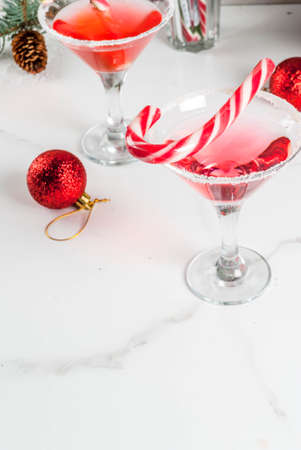 Christmas drinks, pink peppermint martini cocktail with xmas decoration and candy cane sweet on white marble kitchen table, copy space 스톡 콘텐츠