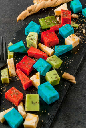lavender coloured: Trendy modern food. Multicolored organic holland cheese - blue (lavender), red (hot pepper), green (basil), classic yellow cheese. With bread sticks, wine glass, black table. Copy space