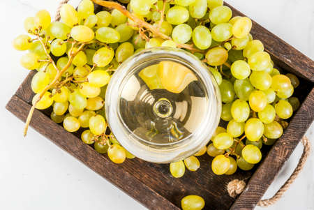 White grapes and white wine in a glass, in a wooden tray on a white marble table. Copy space top view