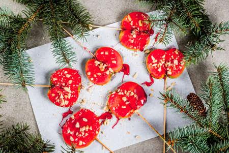 Ideeën van de winter, kersttraktaties. Snoepjes voor kinderen. Chocolade appelschijfjes in rode karamel en noten. Grijze steenachtergrond, met Kerstboomtakken, hoogste mening