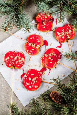Ideas of winter, Christmas treats. Sweets for children. Chocolate Apple Slices in red caramel and nuts. Grey stone background, with christmas tree branches, top view copy space