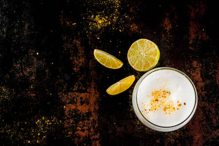 Peruvian, Mexican, Chilean traditional drink pisco sour liqueur, with fresh lime, on rusty black table, copy space top view