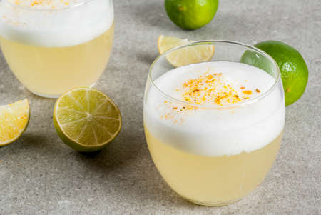 Peruvian, Mexican, Chilean traditional drink pisco sour liqueur, with fresh lime, on gray stone table, copy space Stock Photo