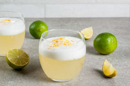 Peruvian, Mexican, Chilean traditional drink pisco sour liqueur, with fresh lime, on gray stone table, copy space 스톡 콘텐츠