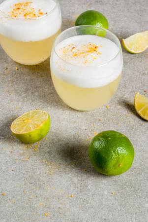 ペルー、メキシコ、チリの伝統的な飲み物ピスコサワー、フレッシュライム、グレーの石テーブル、コピースペース